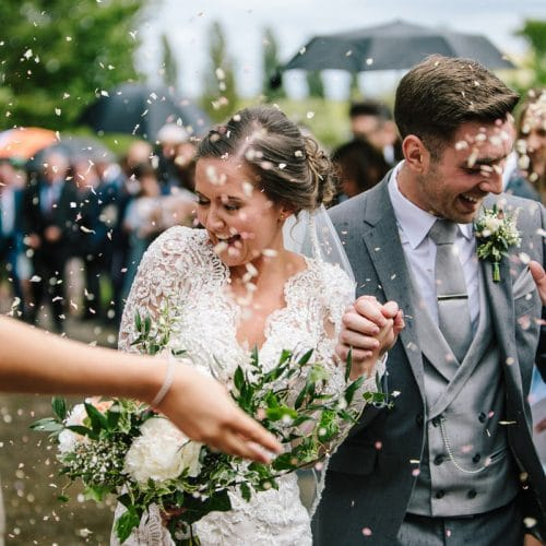 A Beautiful Bride and Groom who has just got married at Dodford Church. Wedding guests are throwing confetti all over them and they are very happy taken by a recommended Dodford Manor wedding photographer