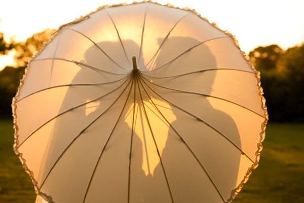 Couple Kissing at sunset against an umbrella at Wethele Manor Warwickshire