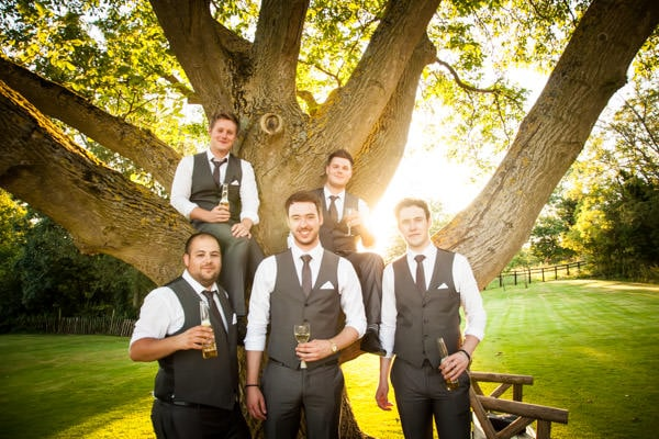 Groomsmen enjoying a drink at sun down sitting in a tree at Crockwell Farm