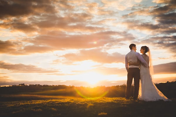 Beautiful Wedding Photograph of a newley wed couple standing in a field watching the sun go down. Photo taken in the fields at Dodford Manor Wedding Venue