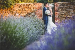 Photography of a couple embracing outside Dodford Manor, next to lots of Lavendar