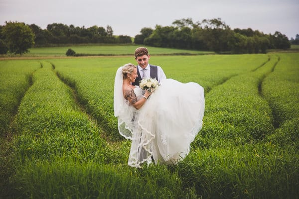 Beautiful photo of the Bride being carried in a field at Crockwell Wedding Venue by her Groom