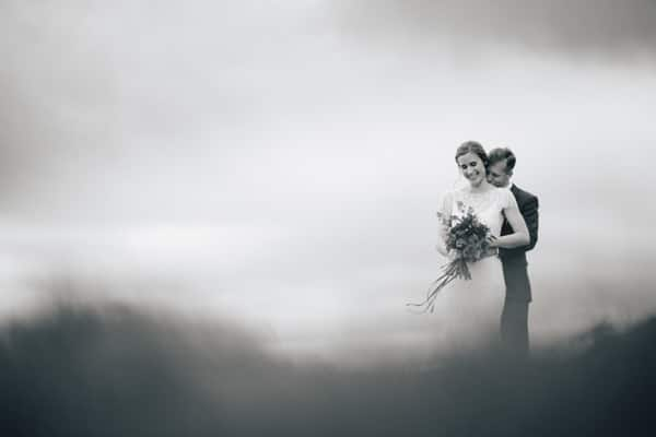 Couple standing in the Sheep fields at a Dodford Manor Wedding, Wedding Photographers Northamptonshire