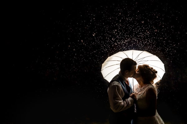 Beautiful photo of a couple standing under an umbrella in the rain at Dodford manor