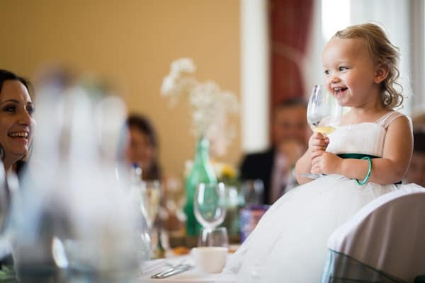Photo of a little girl laughing during the speeches at a wedding at Fawesly Hall