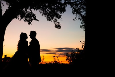 Walnut Tree Inn Wedding Sunset Photo with Bride and Groom kissing under a tree