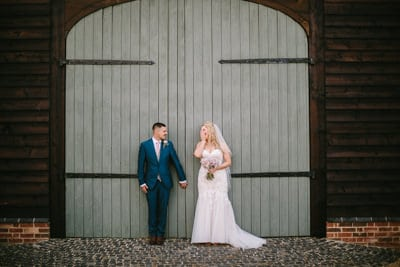Primrose Hill Farm Wedding Bride and groom laughing against a barn door