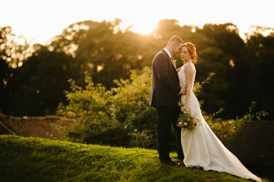 The Barns at Husbury Hill Bride and Groom embracing with sun setting behind them
