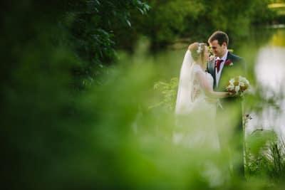 Hellidon Lakes Wedding Bride and Groom kissing next to the lake