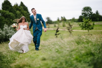 Wedding Couple walking across the fields at Dodford Manor