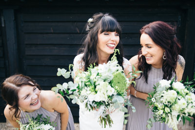 Bride and Bridesmaids laughing at a joke in front of barn doors at a wedding venue in Northamptonshire