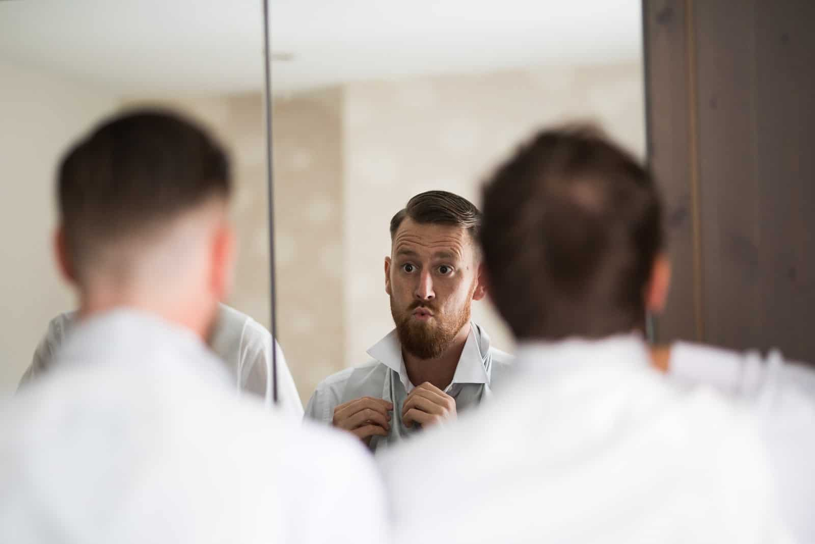 Groomsmen getting ready in a mirror