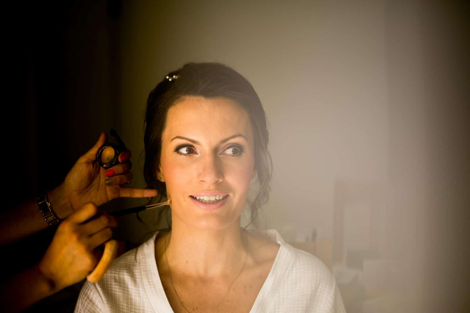 Bride getting ready in the morning hsving her make up applied