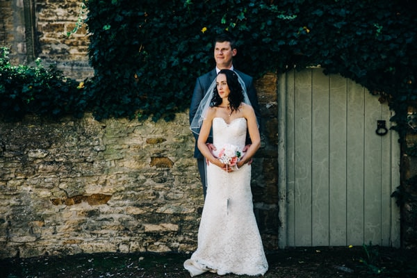 Newly married couple standing outside a church in Northamptonshire