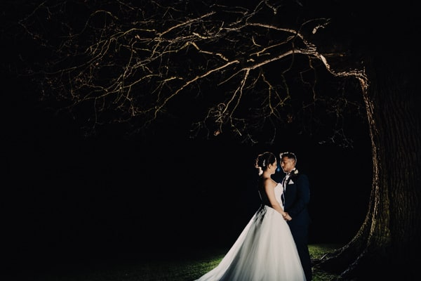 Couple standing together in the dark under a tree at Whittlebury Hall Northamptonshire
