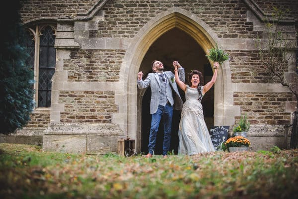 Couple celebrating wildly as they leave the church