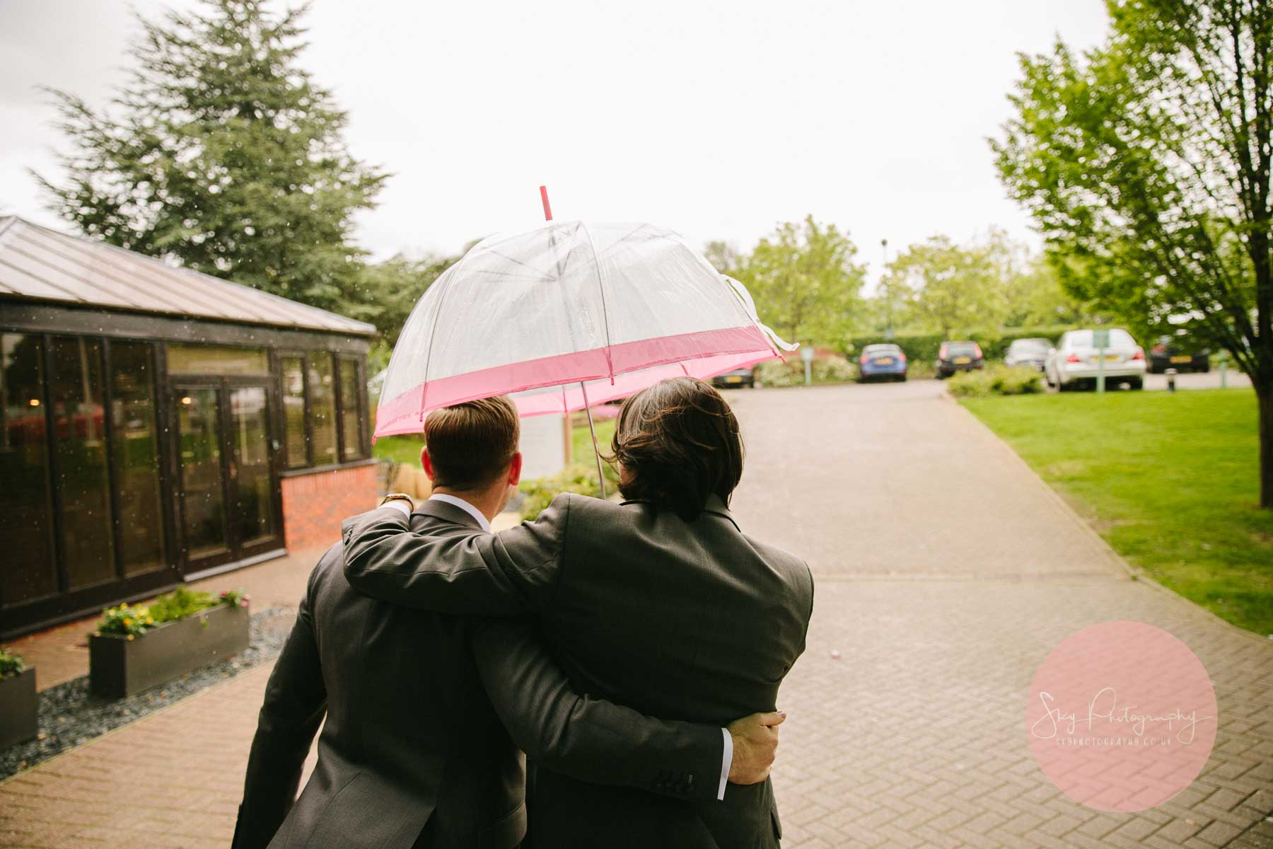Groom being escorted through the rain at Staverton Park hotel on his way to Dodford Manor