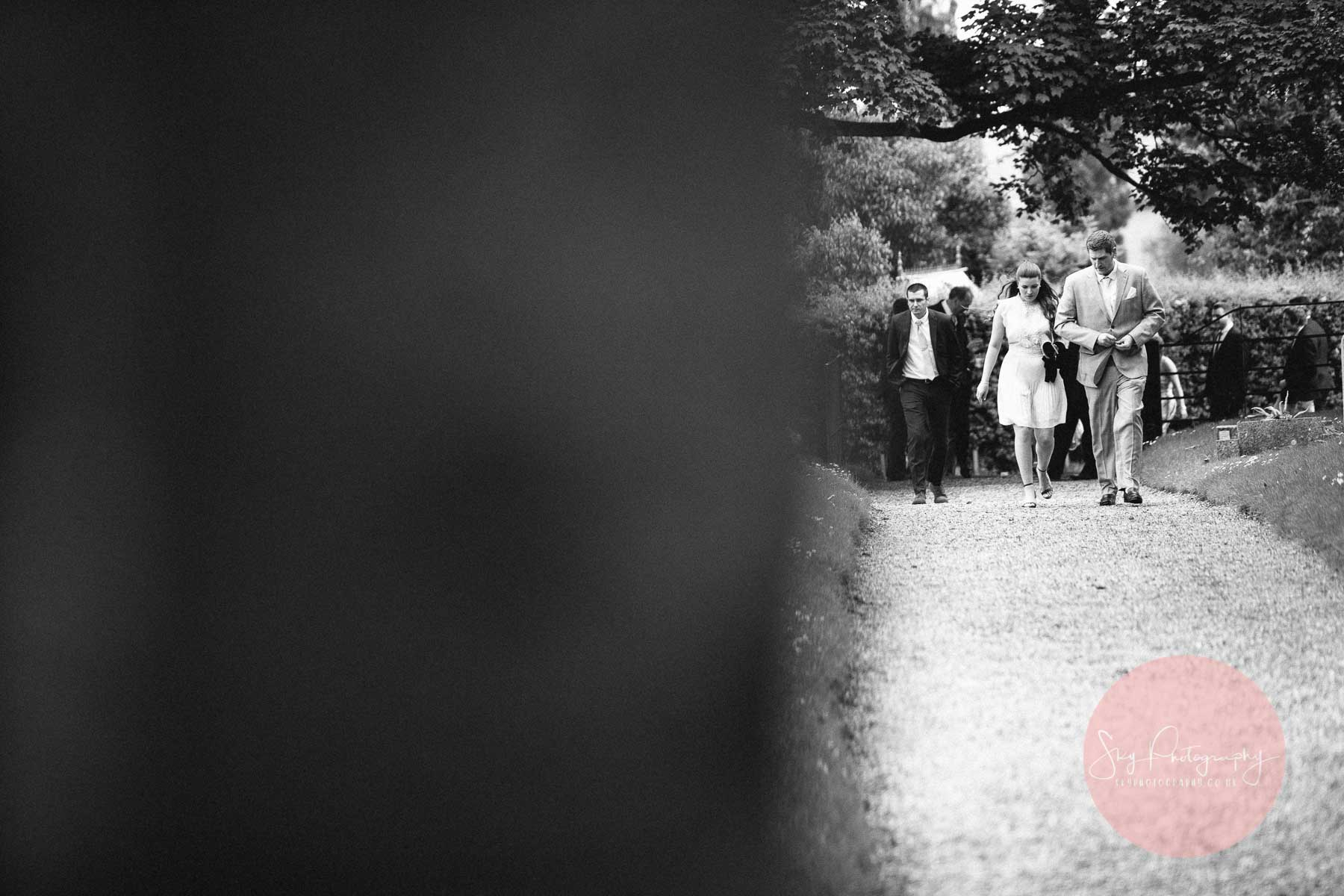 Wedding guests arriving at Dodford Church walking up the path
