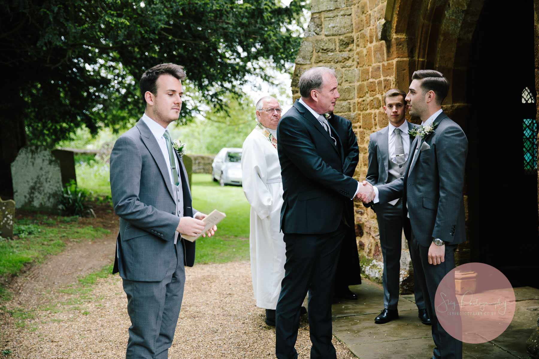 Groom greeting guests outside the Dodford Church