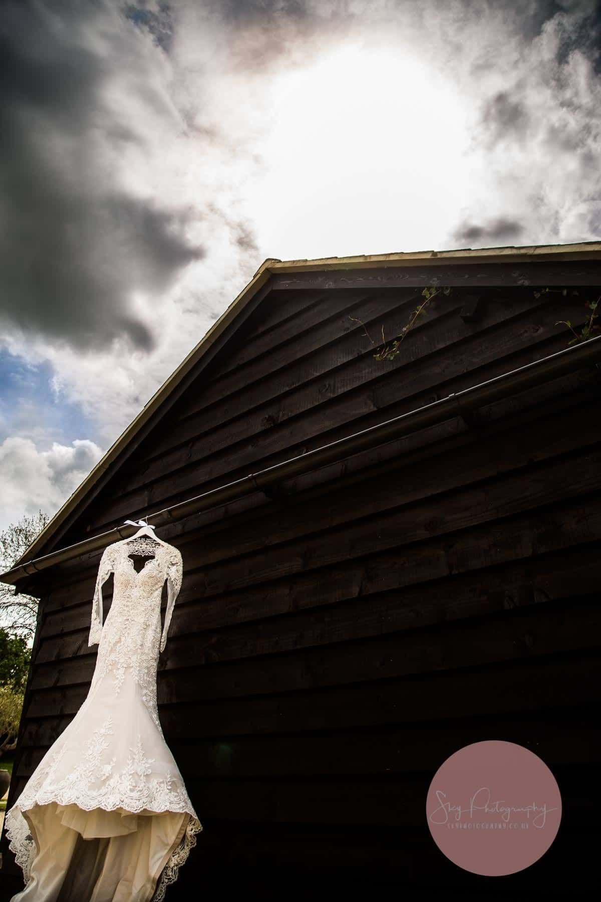 Wedding Dress hanging on the side of a barn at Dodford Manor