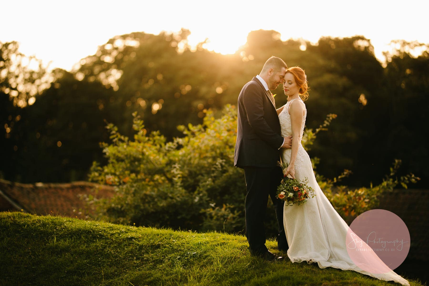 The Barns At Hunsbury Hill Wedding Photographer taking photos of a couple at sunset