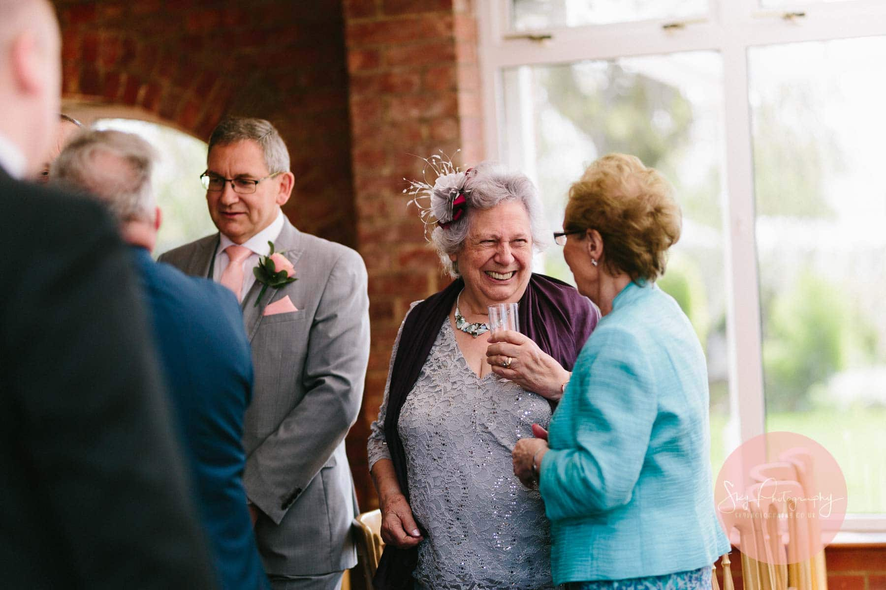 Guests laughing and joking at wedding