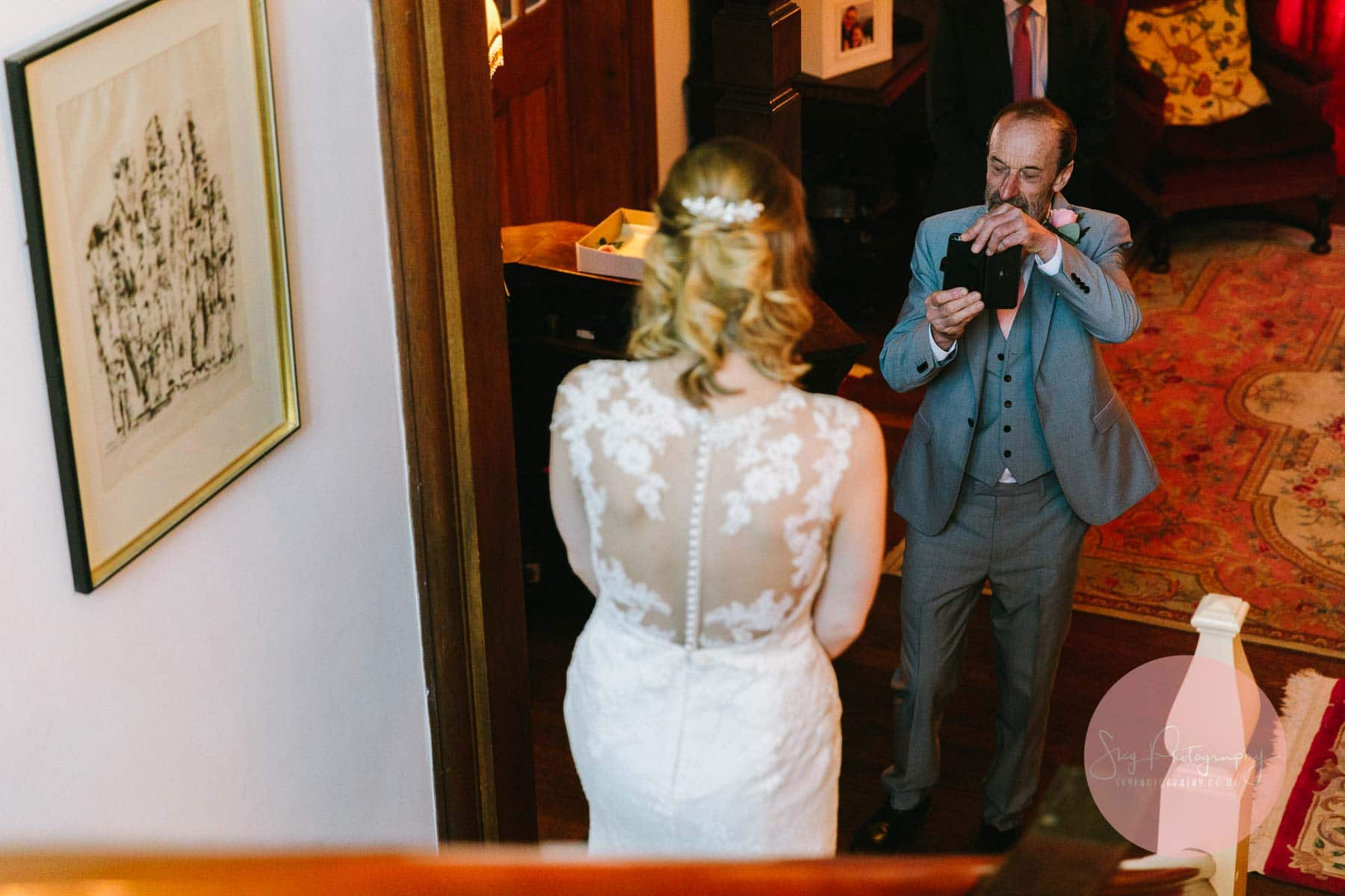 Father of the bride taking photo of his daughter