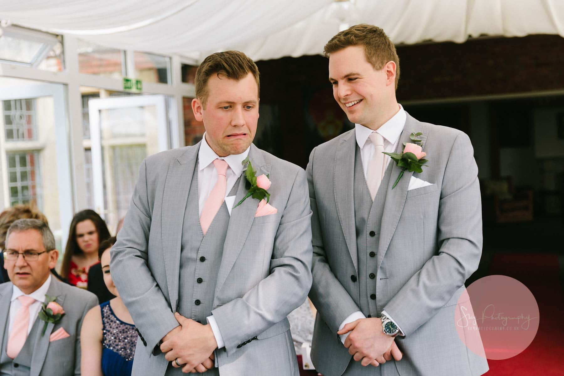 Groom laughing at Best man nervous face