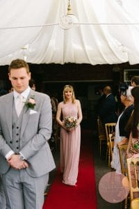 Bridesmaid enter the ceremony room Plum Park with guests looking on