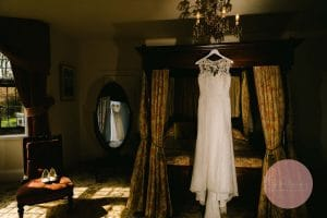 Wedding dress hanging on a a beautiful old bed in the bridal suite at Plum Park