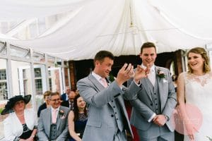 Grooms best man passing the rings to the groom