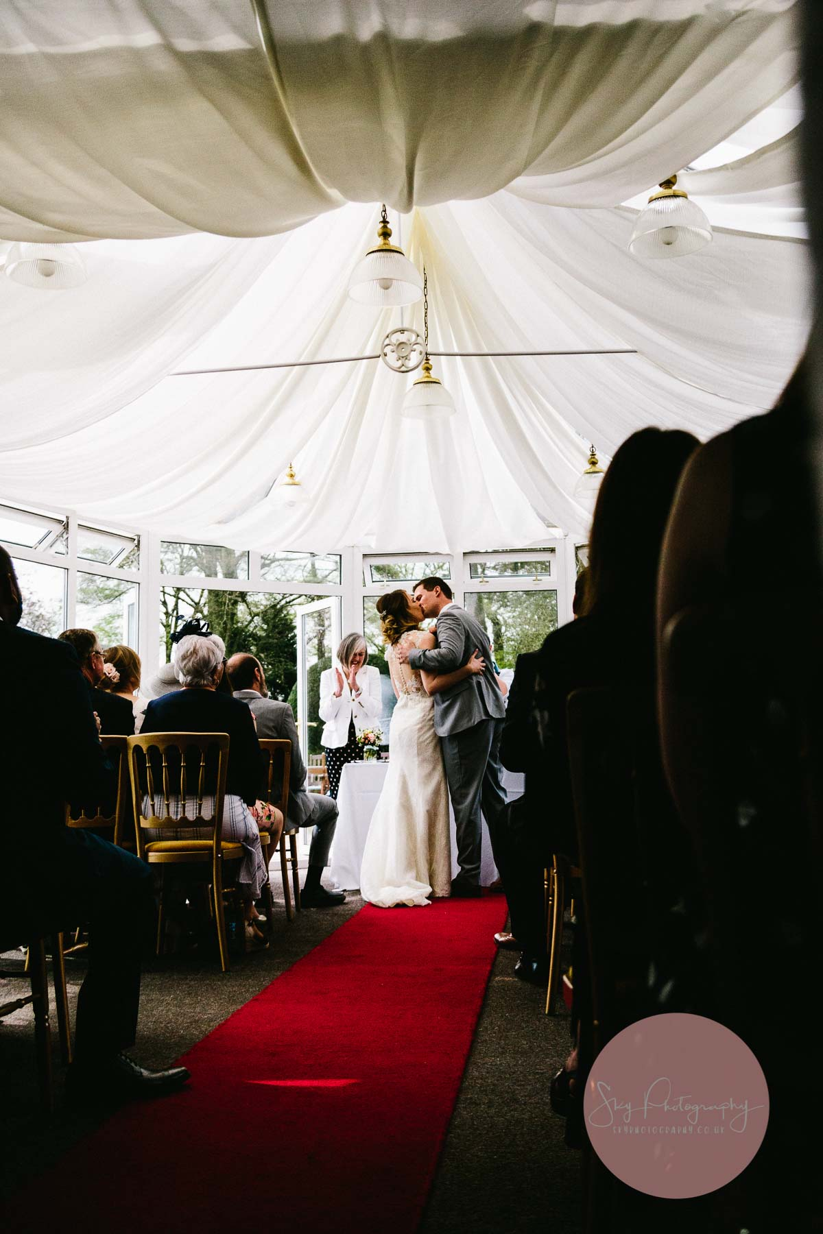 Bride and groom kissing whilst the wedding guests look on at Plum Park