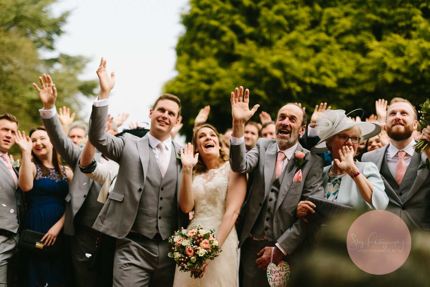 Wedding guests waving whilst having their photo taken