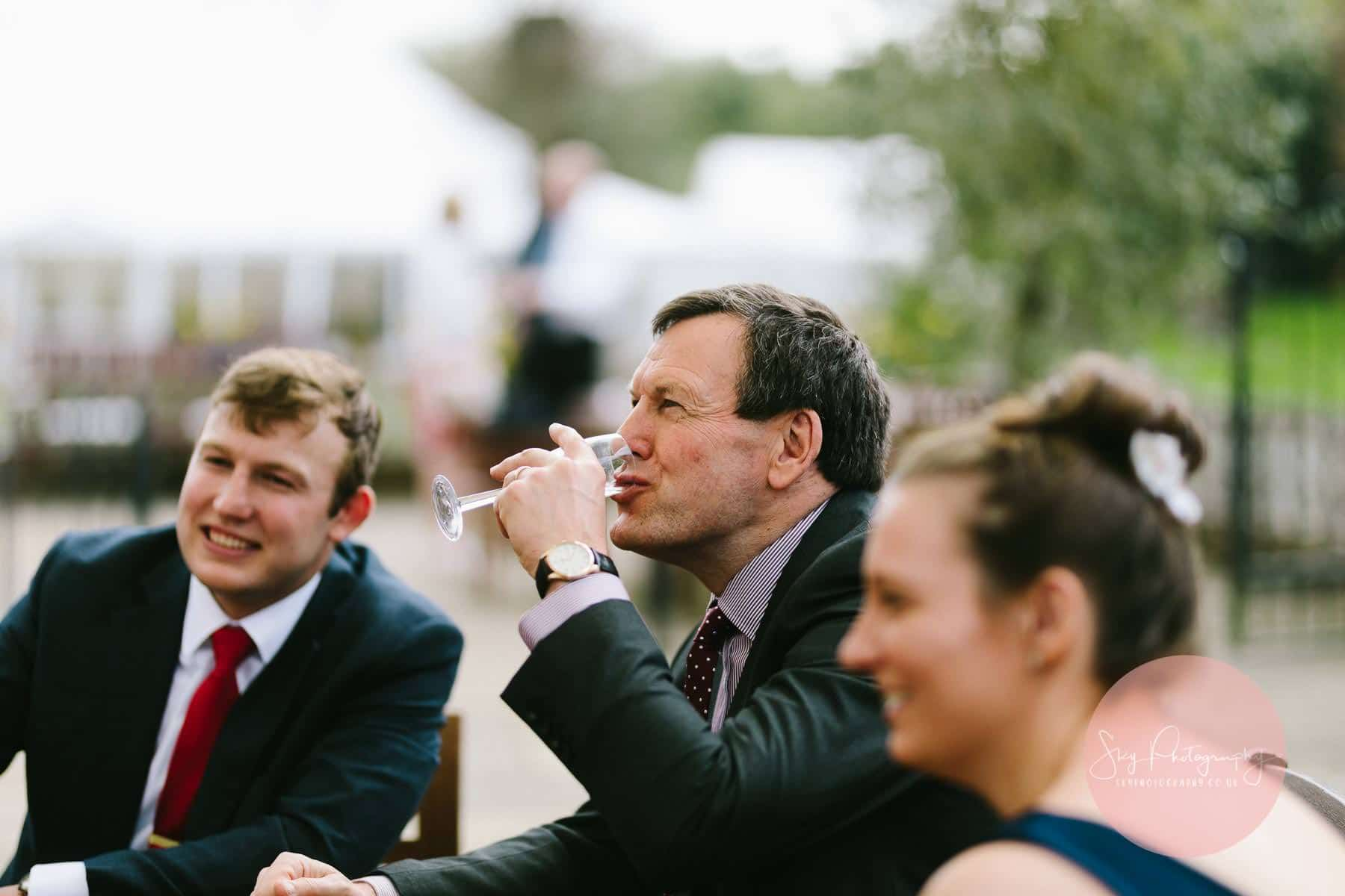 Male wedding guest drinking champagne