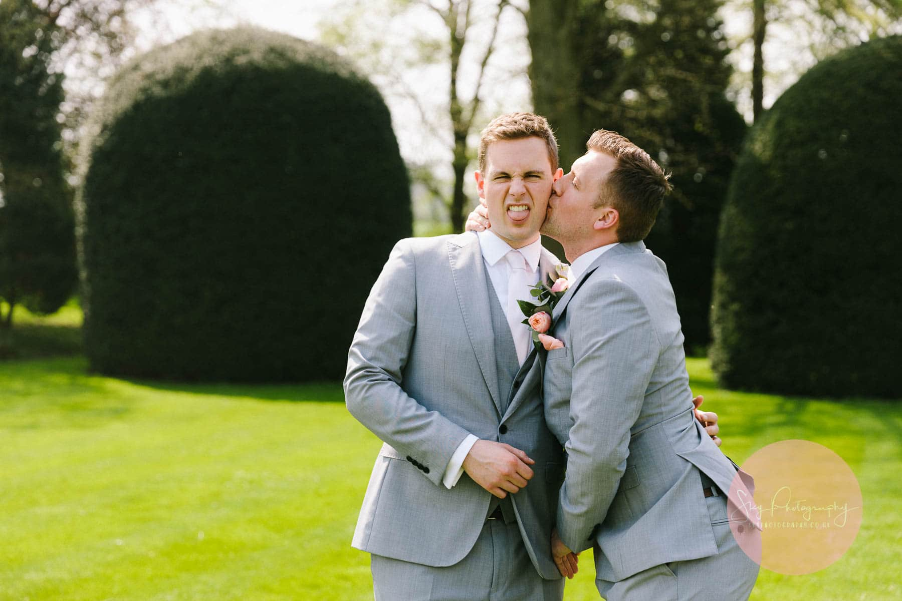 Best man kissing the groom