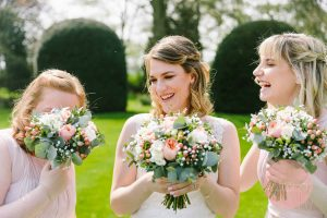 bridesmaids laughing behind flowers