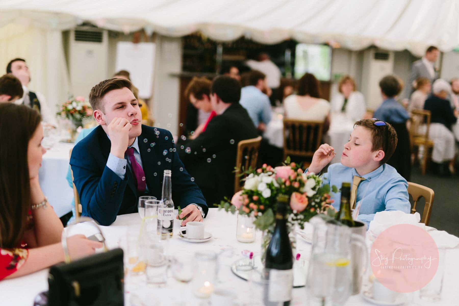 Guest blowing bubbles at wedding reception