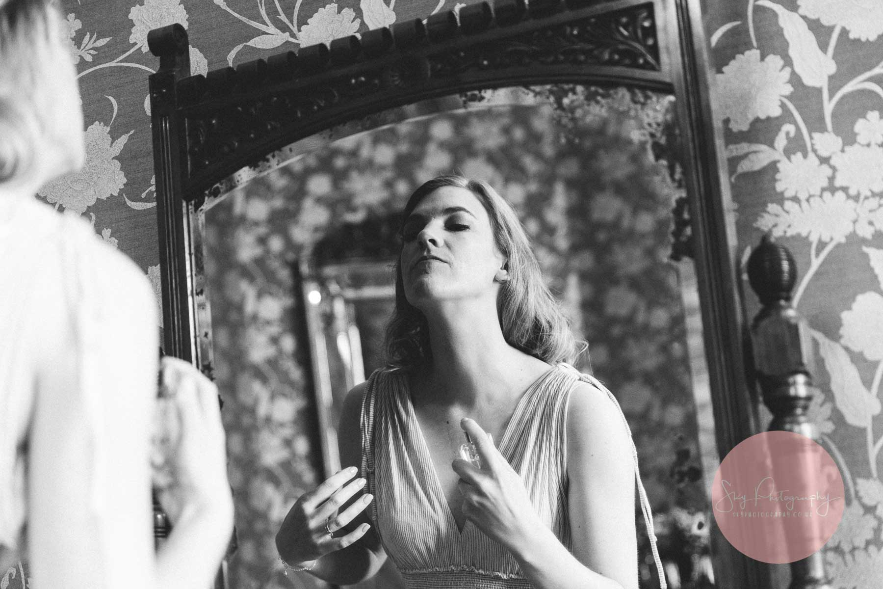 Bride spraying perfume whilst getting ready for her wedding