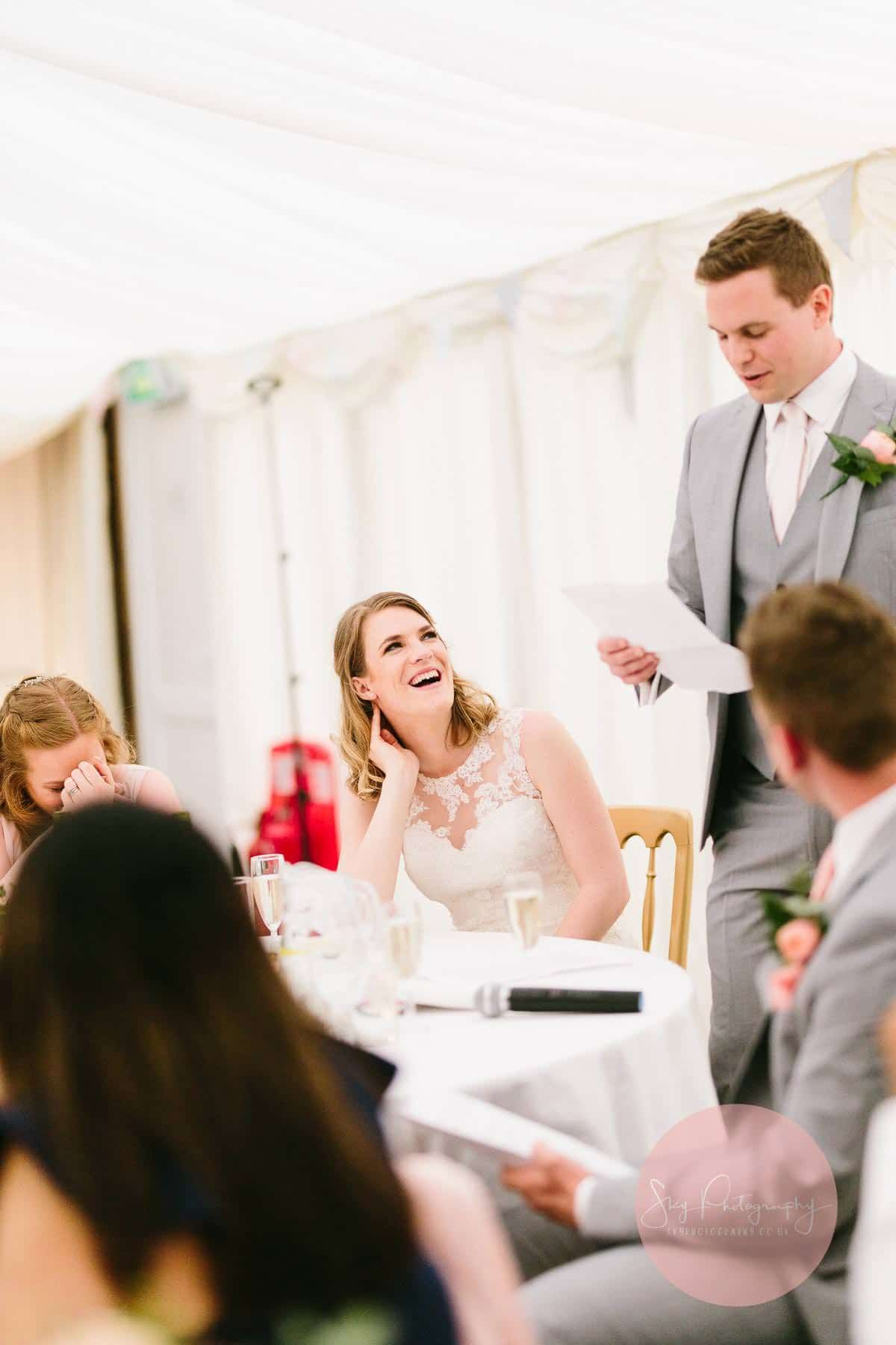 The bride laughing at the groom as he speaks to their guests