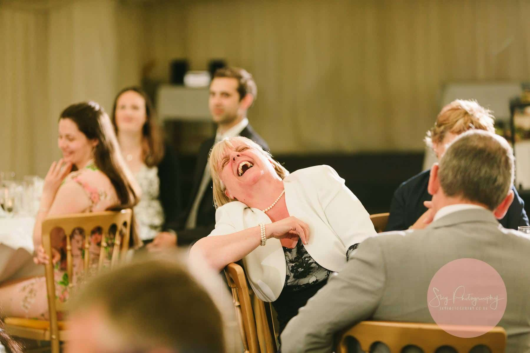 Grooms mother laughing hysterically at the best mans jokes