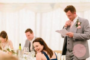 Best man laughing whilst delivering his speech at the wedding reception