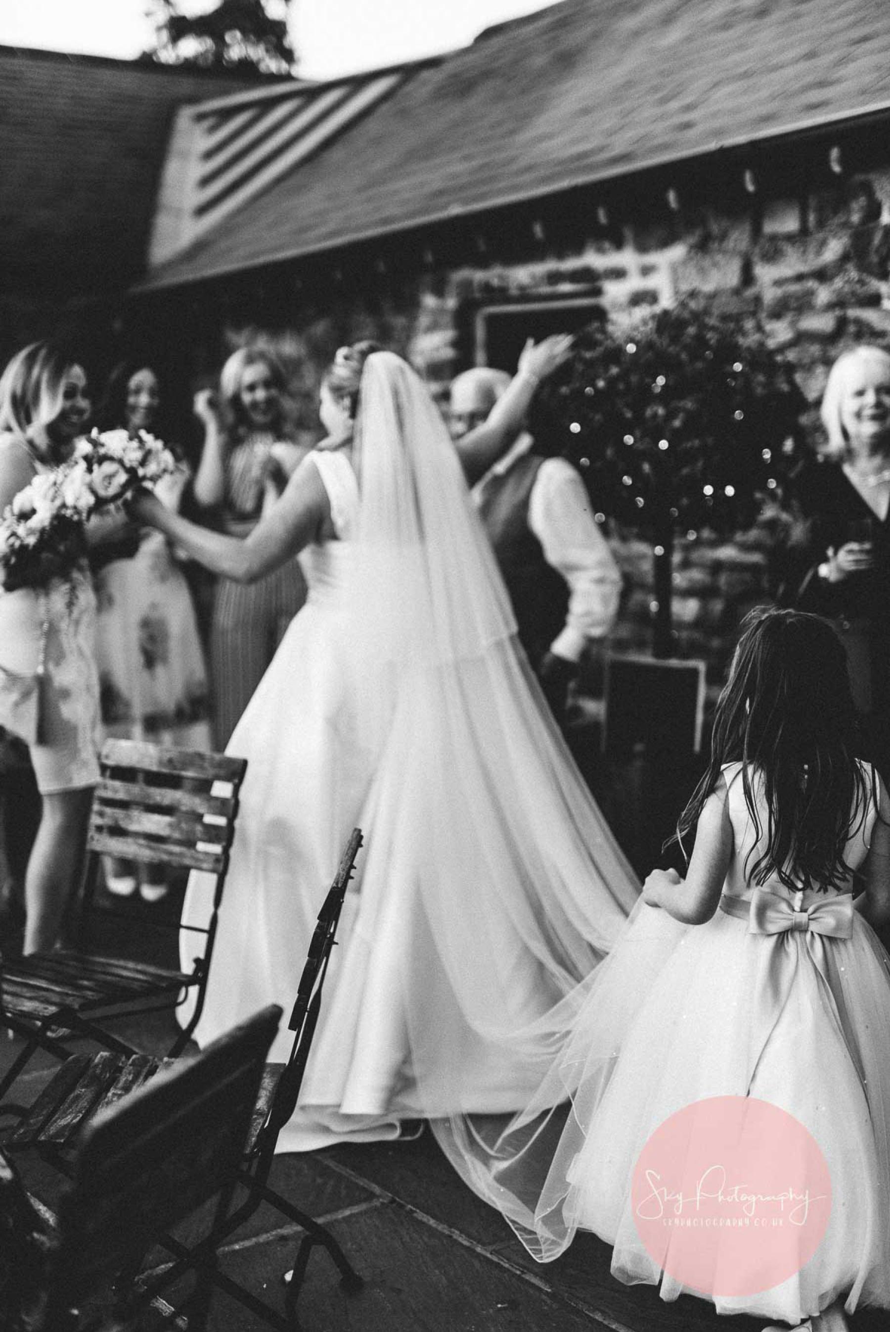 Flower girl holding the brides dress