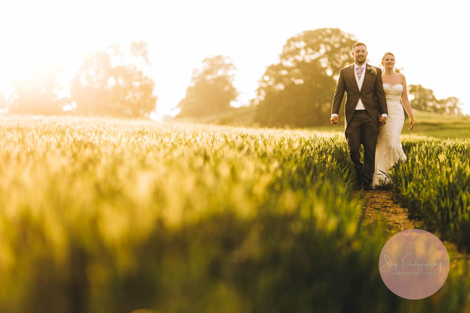 Bride and groom walking through a corn field