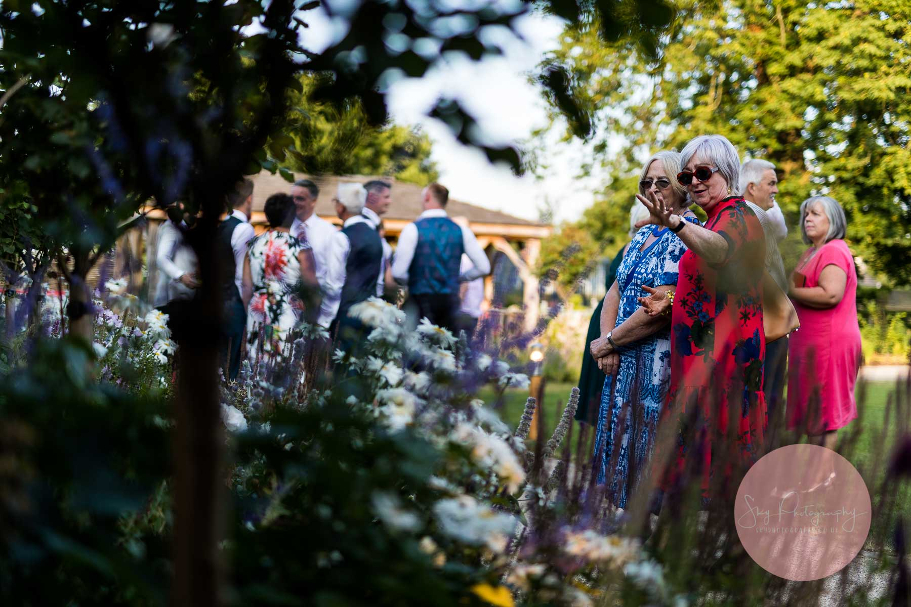 Wedding guests admiring the gardens at Bassmead Barns
