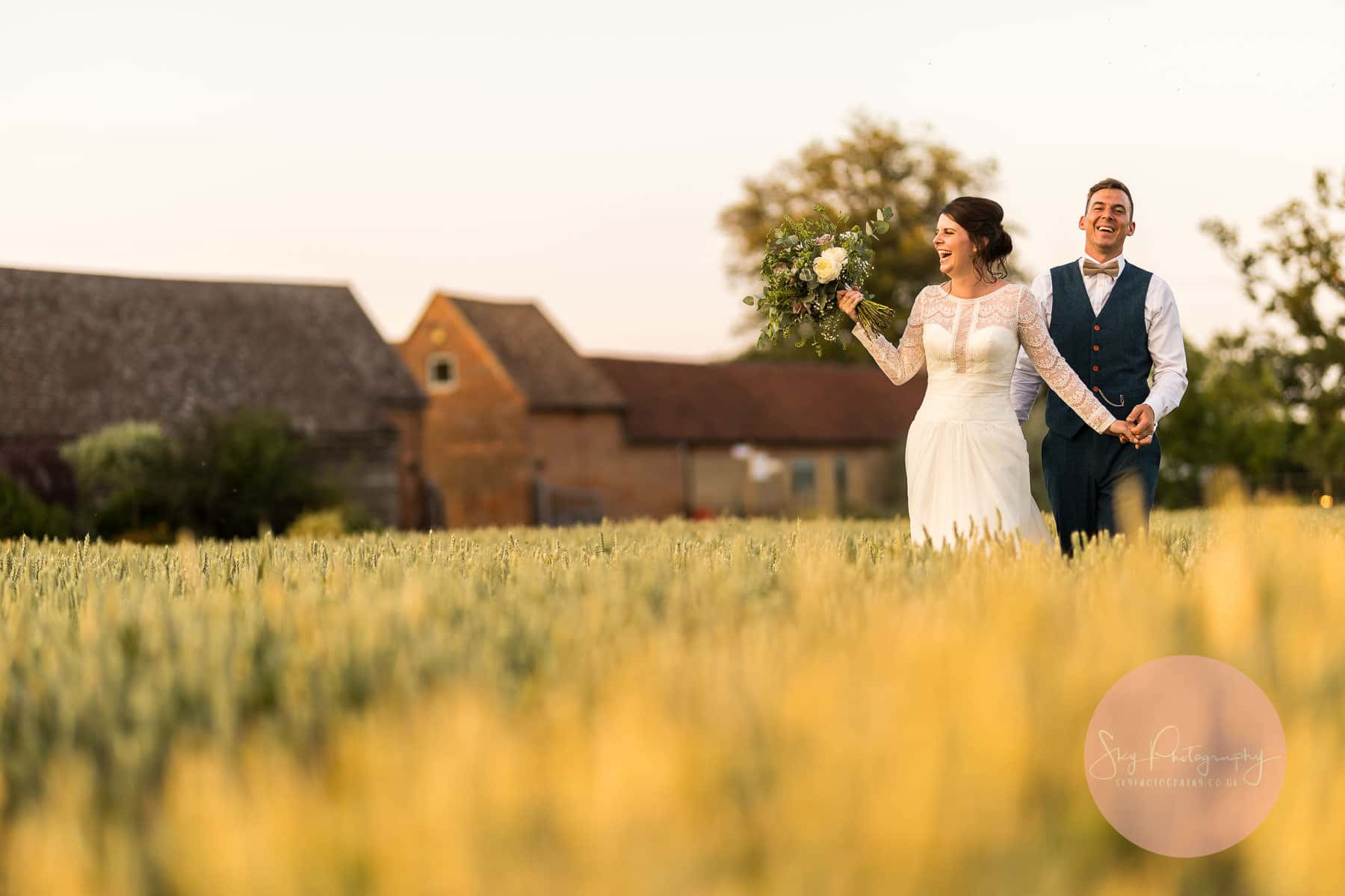 Couple standing in the fields at bassmead barns