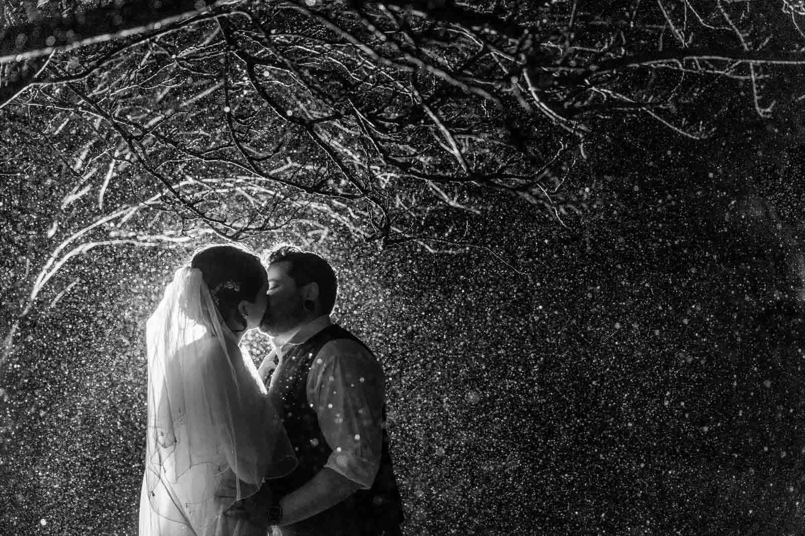 Bride and groom kissing in the rain without umbrella