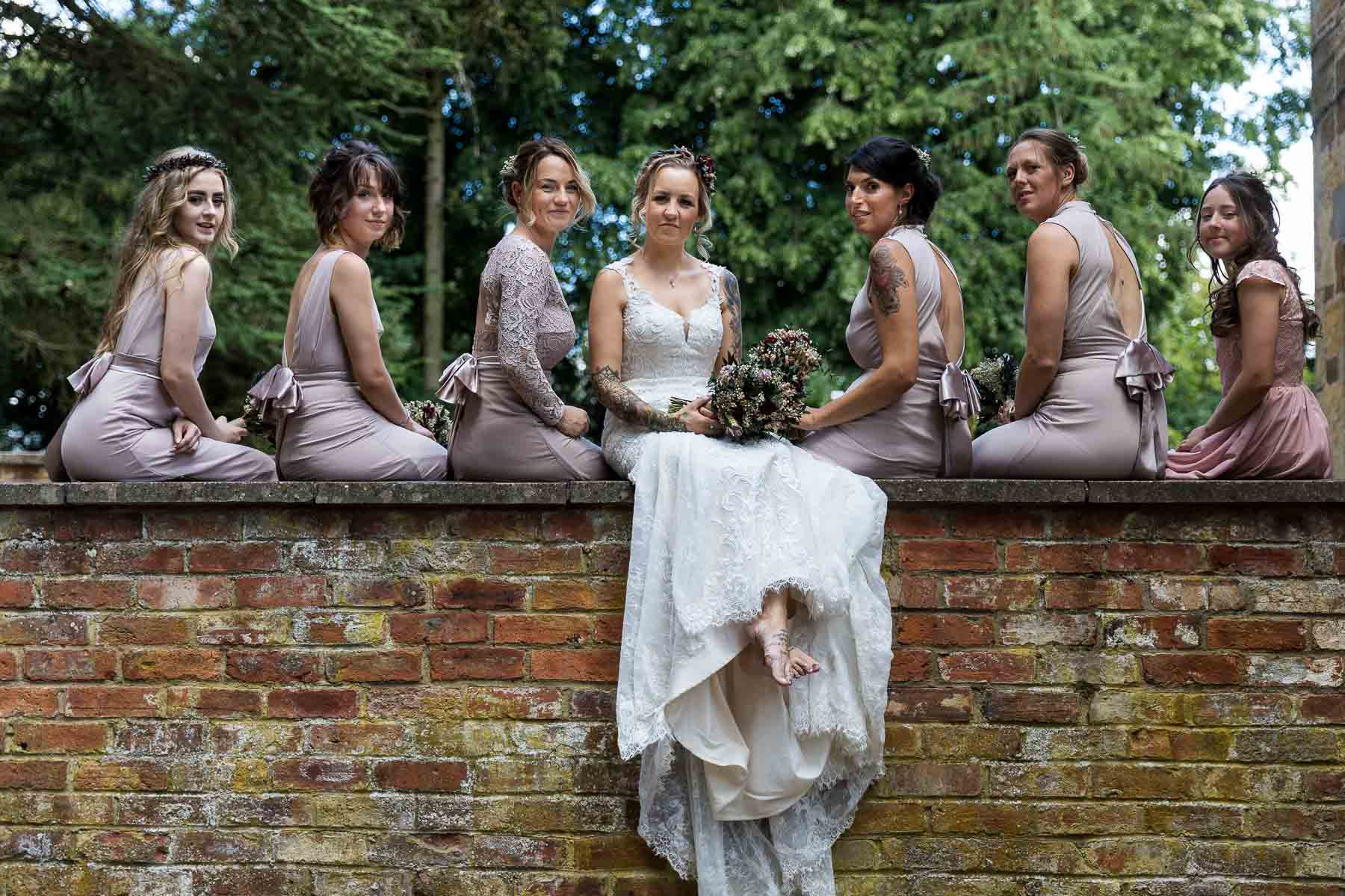 bridesmaids and bride sitting on a wall