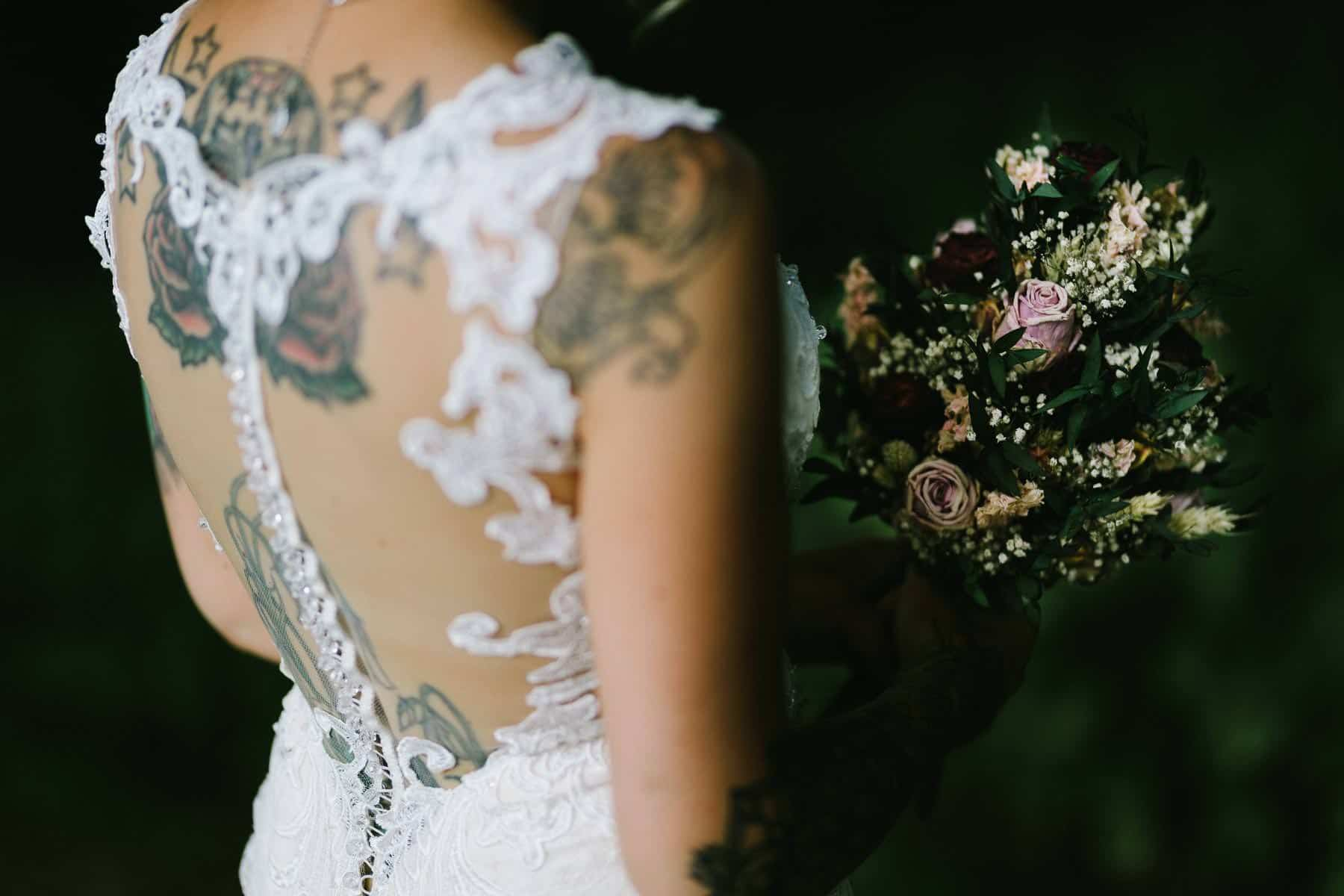 Photo of just the brides tattooed back and her flowers