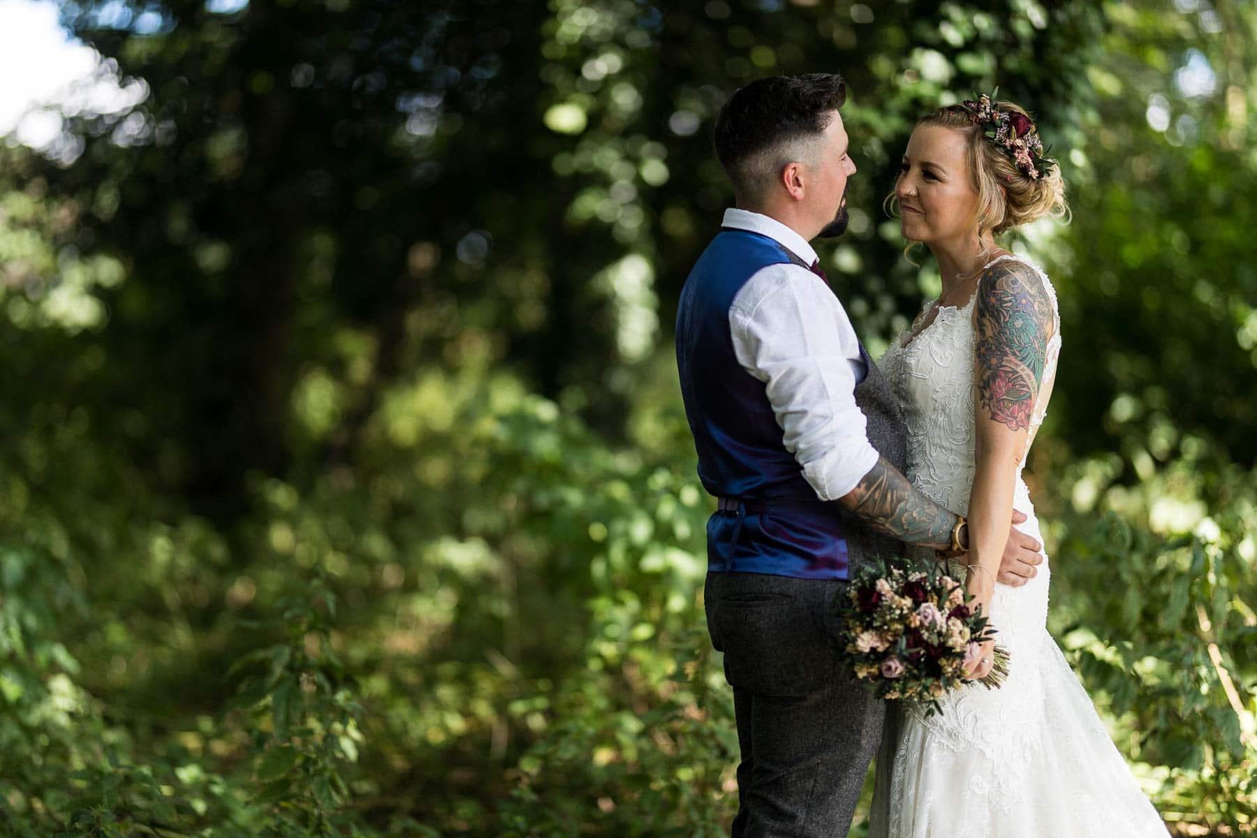 Groom holding his tattooed bride