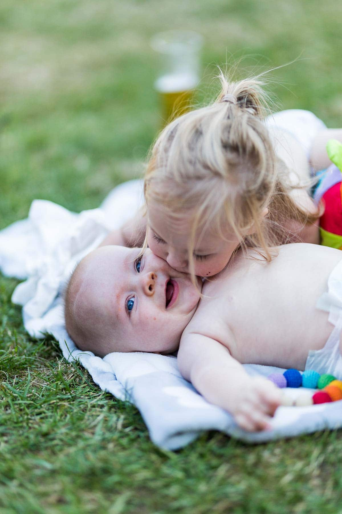 little sister kissing her baby brother